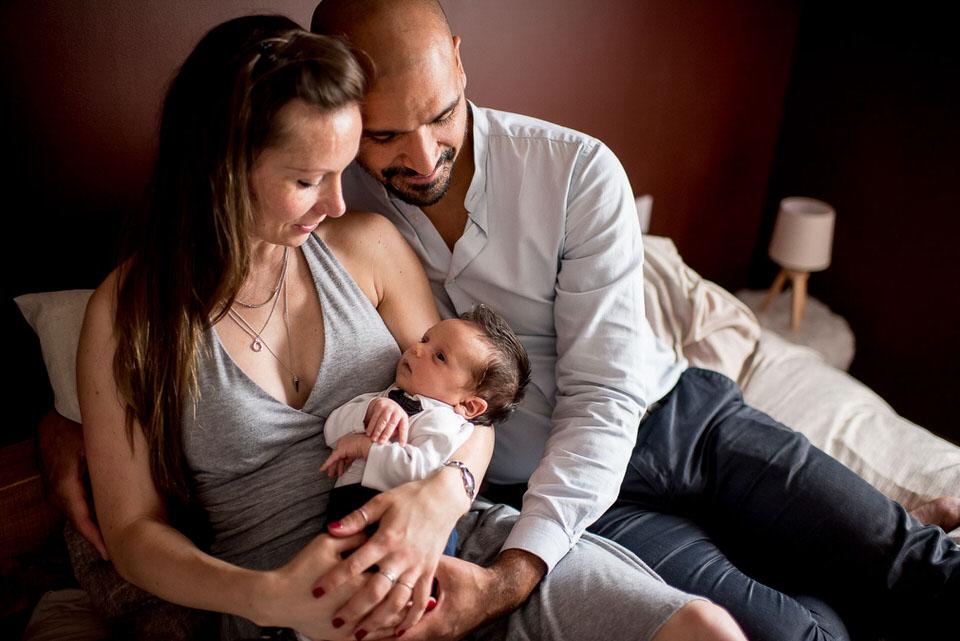 couple nouveau né dans les bras de ses parents