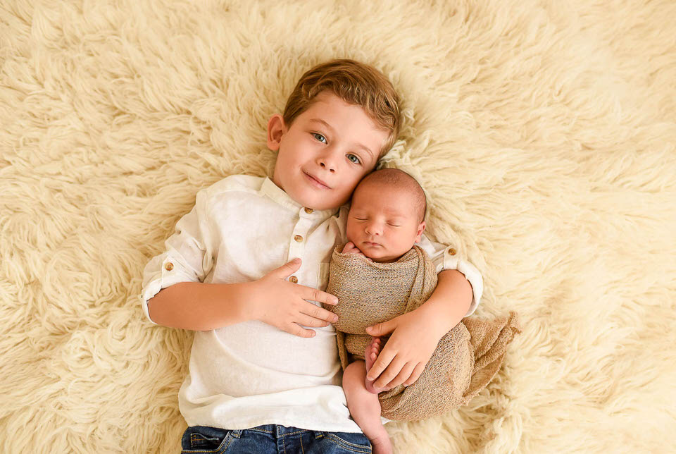 séance photo nouveau né dans les bras de son grand frère studio photo rennes