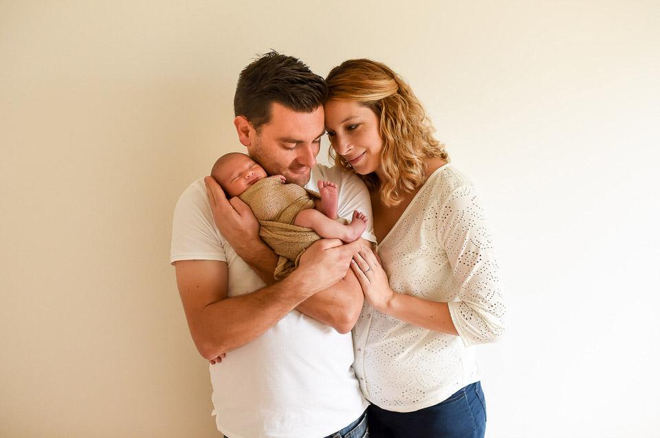 nouveau né dans les bras de ses parents séance photo en studio rennes